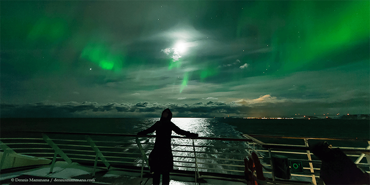 A person on a ship watching the Northern Lights.