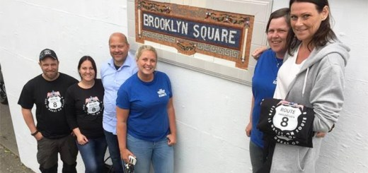 Community members standing in front of the subway sign.
