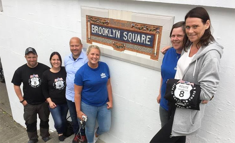 Community members standing in front of the Brooklyn Square subway mural.