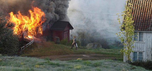 A man walking up to a burning house.
