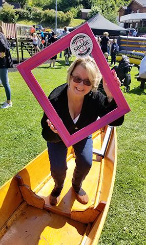 Women in canoe holding pink frame.