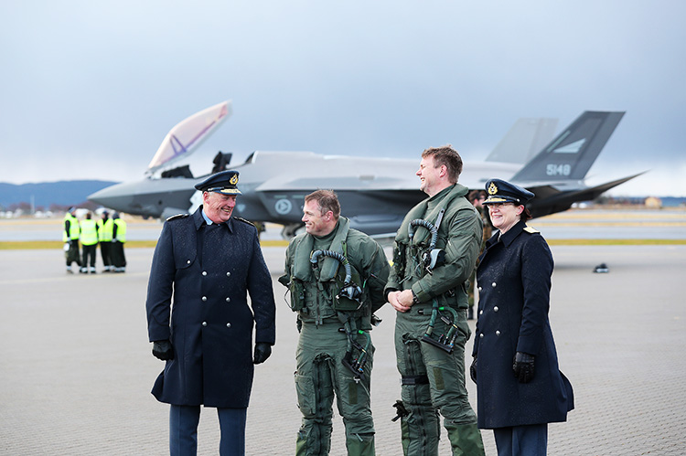 King Harald standing with members of the military in front of the planes.