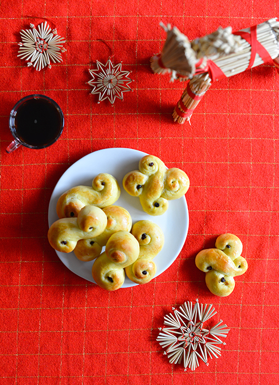 Lussekatter on a plate surrounded by Christmas decorations.