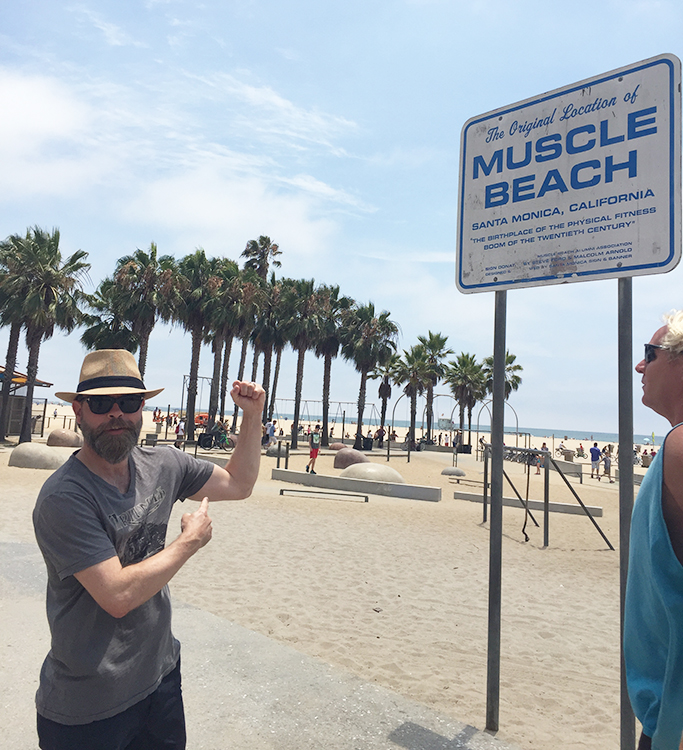 Ørn standing by the Muscle Beach sign.