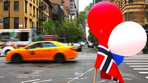 Norwegian flag with balloons on a busy New York street with a yellow cab
