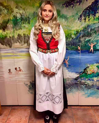 Isrid, the great-granddaughter of Geirr Tveitt, in a red and black bunad with long blond curly hair.