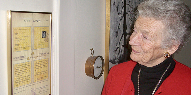 Nina Lagergren, an older woman with gray hair, looks at a framed document