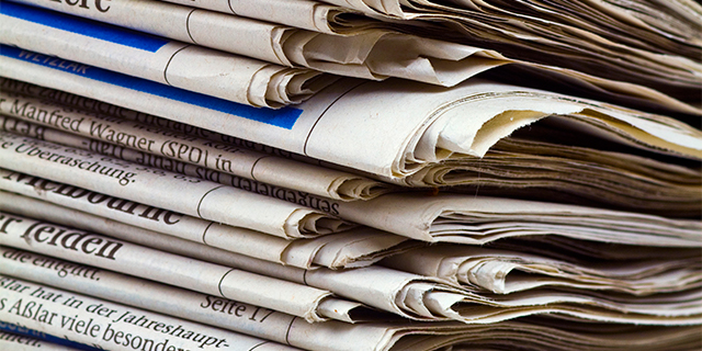 a stack of newspapers representing journalism