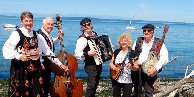 members of the Winter Band in bunads hold their instruments on a beach by the Puget Sound