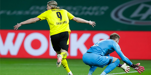 Erling Braut Haaland in a yellow jersey with the number 9 on the back runs with his arms out.