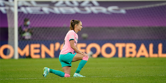 Caroline Graham Hansen kneels on the field wearing a light pink shirt and teal shorts with teal and pink socks.