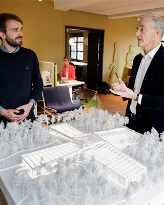 Jan Christian Vestre talks with Jonas Gahr Støre while looking at a building model of Vestre's new furniture factory.