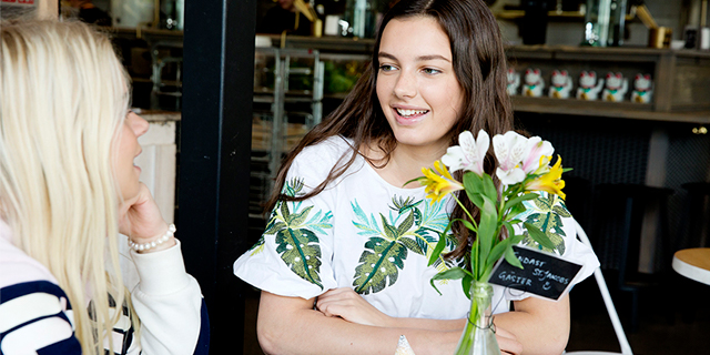 two young white women sit at a table with flowers on it