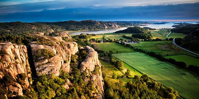a rocky cliff and a view of green fields backed by water in Bohuslän