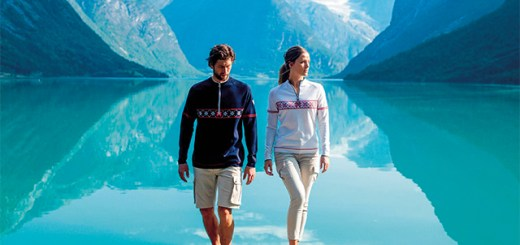 A man and a woman model the new Olympic sweater from Dale of Norway against the backdrop of a fjord and mountains