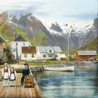 A photograph of two young girls in bunads and a man sitting on a suitcase by the edge of a fjord with mountains in the background