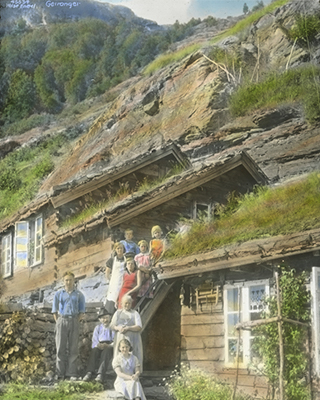 a group of people stand by a cabin in the mountain side in a photo in a new book by Håvard Mossige