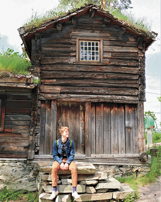 a boy sitting in front of a log cabin