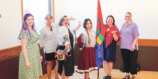 Sandra Andersen Eira with representatives from Leif Erikson Lodge by the Sámi flag