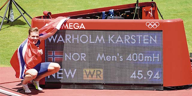 Gold medal winner Karsten Warholm points to his world record breaking time on the screen