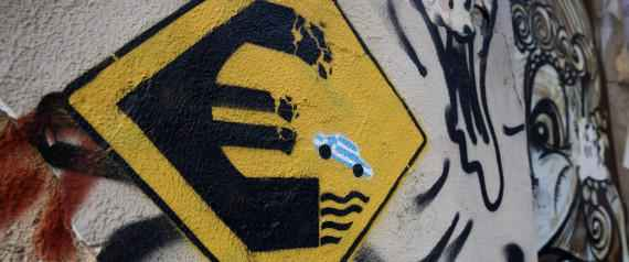 """In this photo taken on Thursday, June 18, 2015 a stencil work by an artist who uses the name Wild Drawing shows a fake road sign with a little car in the blue and white Greek colours tumbling off a crumbling euro currency sign into the water. It's called """"Keep Away."""" Over the past five years of Greece's economic depression, more and more paintings comment on the country's financial and social woes. (AP Photo/Petros Giannakouris)"""