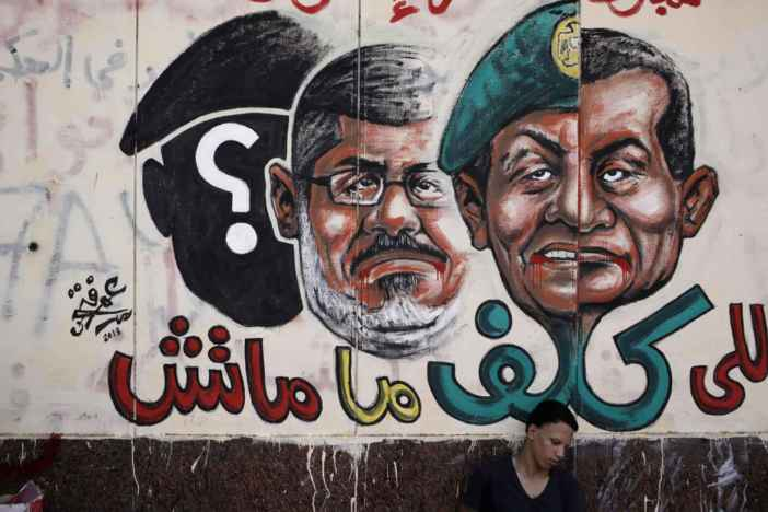 CAIRO, EGYPT - JULY 3: An opposition demonstrator sits below graffiti of Egyptian President Mohammed Morsi on the walls of Egypt's Presidential Palace in the suburb of Heliopolis on July 3 2013, in Cairo, Egypt. The Egyptian Health Ministry reported at least 16 people were killed overnight on July 2 in violent clashes between Pro-Morsi and Anti-Morsi protesters in the Cairo suburb of Giza. An Army ultimatum to President Morsi comes to an end on Wednesday afternoon. In a statement on July 1, the Egyptian Army asked Egyptian President Mohammed Morsi to resolve mass demonstrations against his continued rule or face intervention by the military within 48 hours, after millions of Egyptians took to the streets to protest Morsi's rule on June 30. (Photo by Ed Giles/Getty Images).