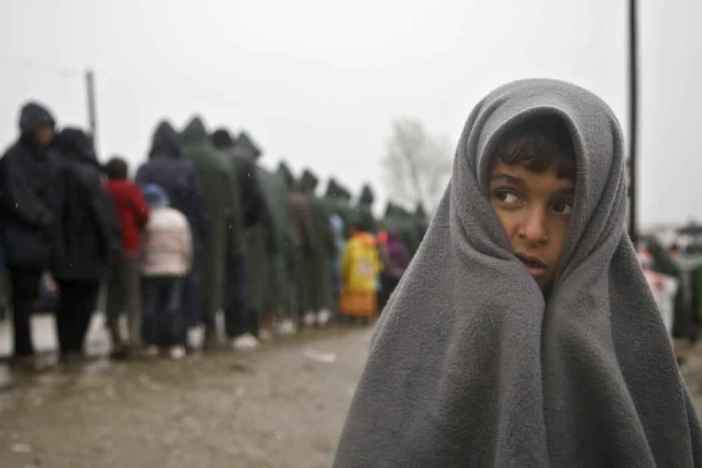 Migrant child covered in blanket stands in rain at the Greek border camp near Idomeni, Thursday, March 10, 2016. Northbound borders are closed and authorities plan to distribute fliers telling refugees seeking to reach central Europe that  there is no hope of you continuing north, therefore come to the camps where we can provide assistance  as more than 36,000 transient migrants are thought to be stuck in financially struggling Greece. (AP Photo/Visar Kryeziu)