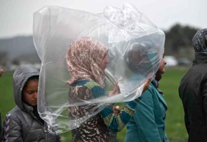 A migrant girl shields herself from the rain while waiting in a line for food rations at the northern Greek border station of Idomeni on March 7, 2016. Greek police officials say Macedonian authorities have imposed further restrictions on refugees trying to cross the border, saying only those from cities they consider to be at war can enter as up to 14,000 people are trapped in Idomeni, while another 6,000-7,000 are being housed in refugee camps around the region. (AP Photo/Vadim Ghirda)