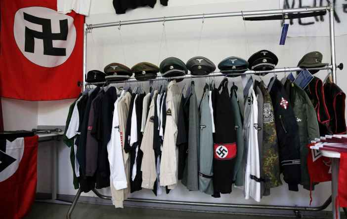 Nazi uniforms and a Swastika flag that were confiscated by the Berlin police during raids against German neo-Nazis are presented to the public during an open day at a police barracks in Berlin, September 7, 2014.  REUTERS/Fabrizio Bensch (GERMANY - Tags: SOCIETY) - RTR459L6