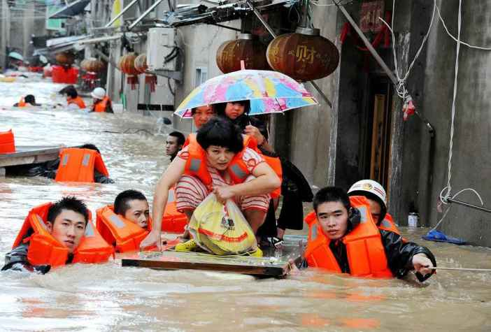 TOPSHOT - Rescuers evacuate residents through floodwaters brought by typhoon Megi in Ningde, eastern China's Fujian province on September 28, 2016. Typhoon Megi smashed into the Chinese mainland on September 28 morning, killing one person, after leaving a trail of destruction and four people dead in Taiwan. / AFP / STR / China OUT        (Photo credit should read STR/AFP/Getty Images)