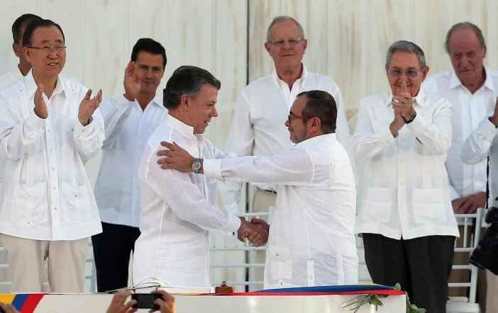 Colombia's President Juan Manuel Santos, front left, and the top commander of the Revolutionary Armed Forces of Colombia (FARC) Rodrigo Londono, known by the alias Timochenko, shake hands after signing the peace agreement between Colombia's government and the FARC to end over 50 years of conflict in Cartagena, Colombia, Monday, Sept. 26, 2016. Behind, from left, are U.N. Secretary General Ban Ki Moon, Mexico's President Enrique Pena Nieto, Peru's President Pedro Pablo Kuczynski, Cuba's President Raul Castro, and Spain's former King Juan Carlos. (AP Photo/Fernando Vergara)