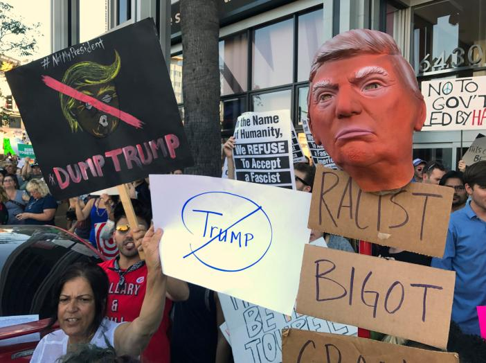 Protesters hold banners during a rally outside the CNN studios, in opposition to President-elect Donald Trump, in the Hollywood section of Los Angeles on Sunday, Nov .13, 2016. (AP Photo/Damian Dovarganes)