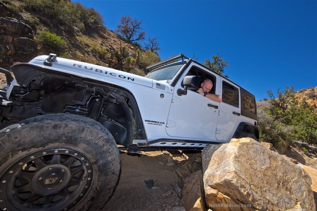 White Jeep going over rocks