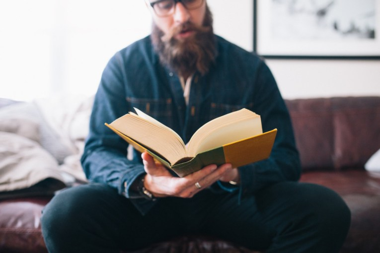 man reading a big book