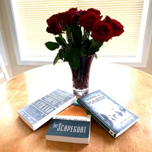 vase of roses with 3 books by Daphne du Maurier: The Scapegoat, The House on the Strand, The Birds and Other Stories