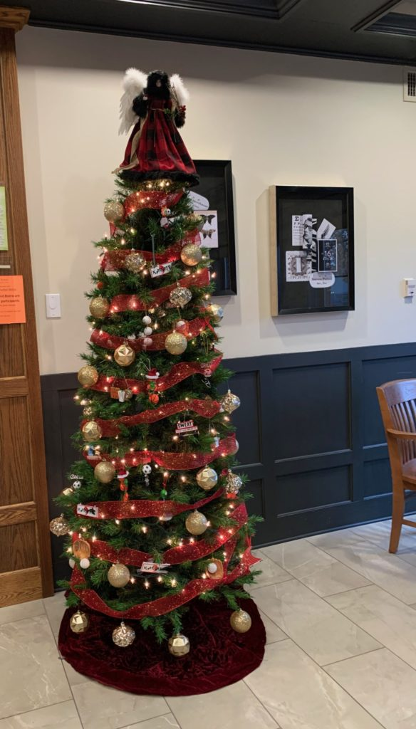 tall Christmas tree decorated with gold balls, red ribbon, and a Victorian angel on top