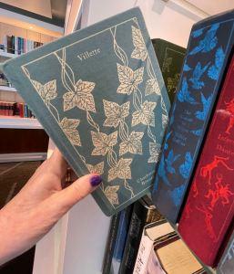 "hand pulling book ""Villette"" from shelf"