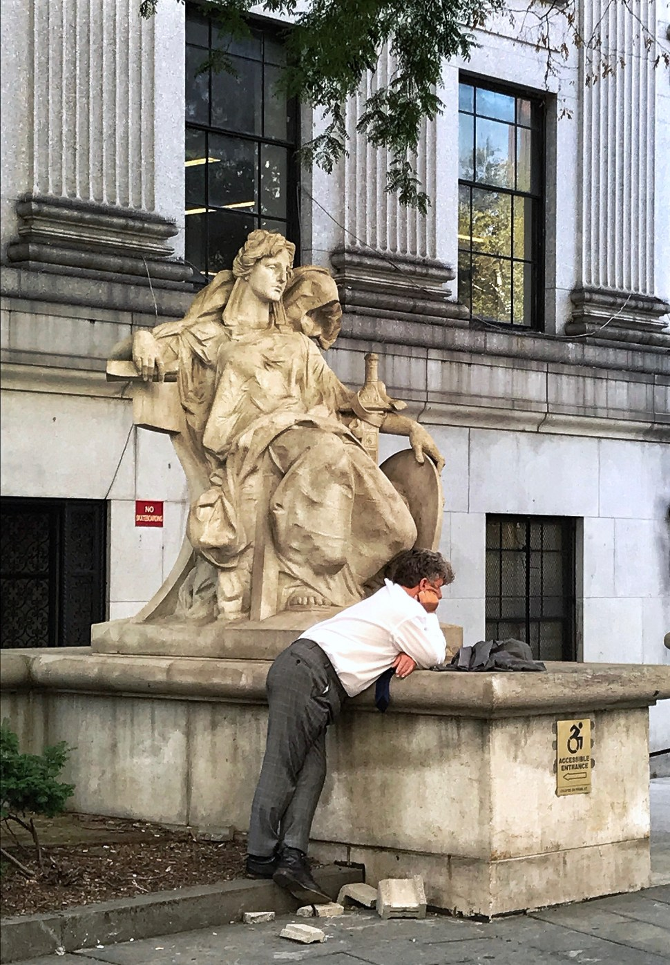 "The statue of ""Justice"" reclines near the rear entrance of the New York State Supreme Court Building. Photo by Rick Stachura. August 15, 2019."
