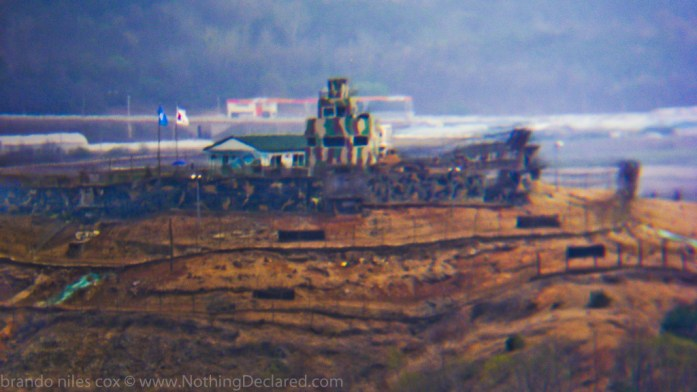 From atop a hill on the North Korean side of the DMZ, you could spy on Joint South Korean / USA / UN military instalations in South Korea by using creepy powerful binoculars.