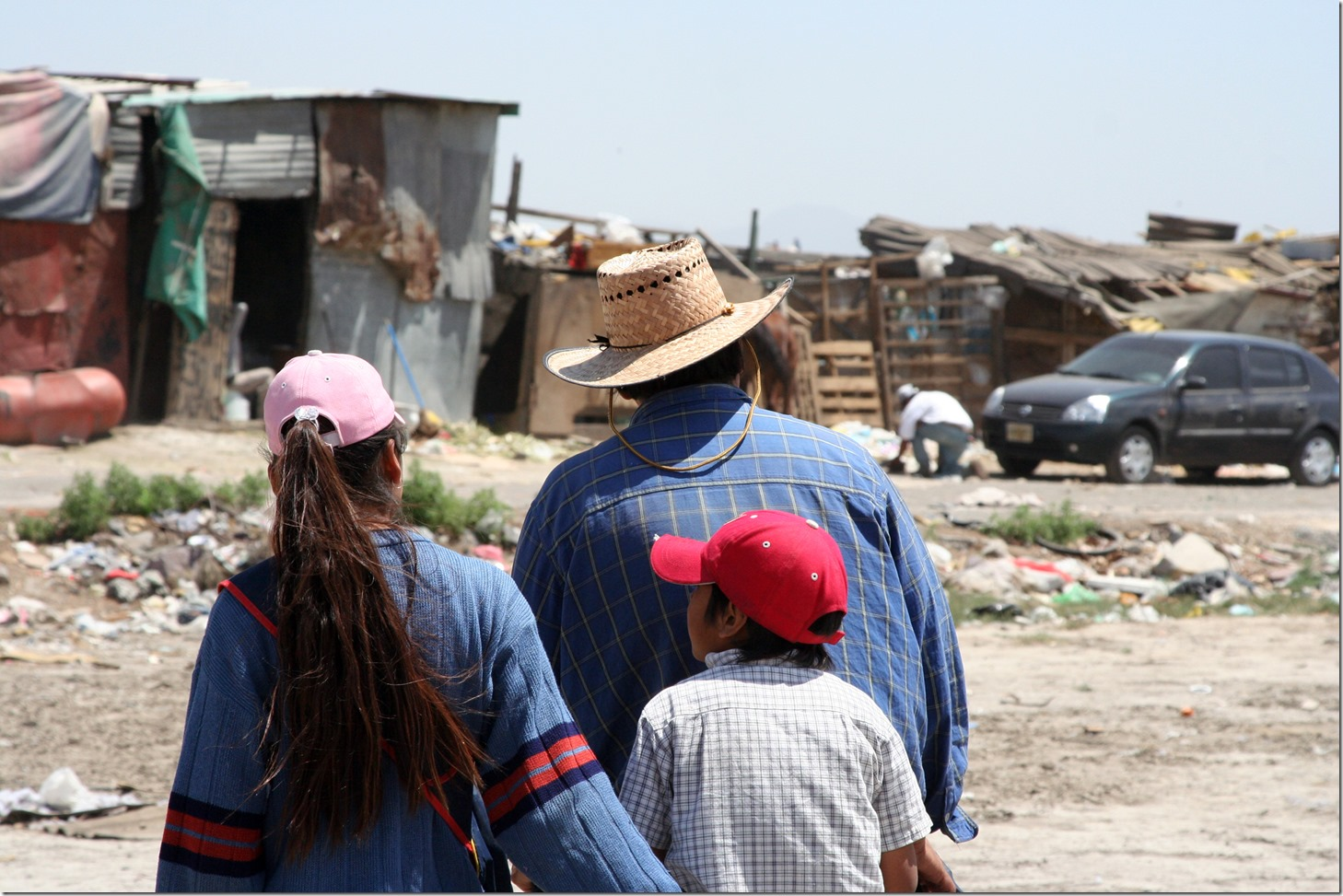 A family is walking to their home at a garbage dump.