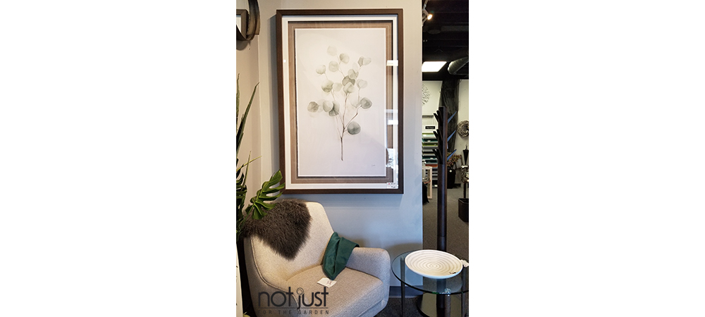 Artwork with branch and leaves set in a brown wooden frame over a nestled upholstered accent armchair and side table