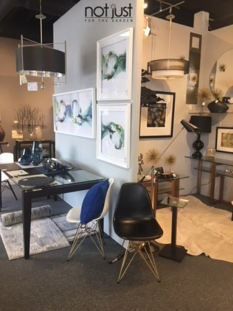 Contemporary furniture in an interior decor setting with three framed art pieces on the walls and a dining table with black and white eiffel chairs and a pendant light