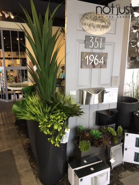 Contemporary outdoor decorative accents with large black outdoor planter with faux plants, front entrance door with metal on stone door number plates and stainless steel mailboxes