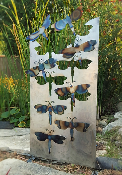 Outdoor sculptural metal art of dragonfly cutouts