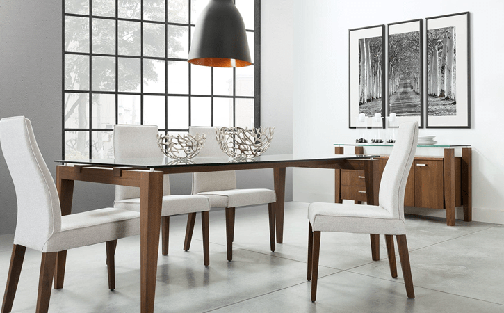 Dining room interior decor setting with white upholstered dining chairs, glass dining table, credenza and wall art by Canadian furniture company, Verbois