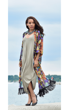 Trendy women apparel casual wear Kimono by Rapz with black fringe worn by a woman by the beach