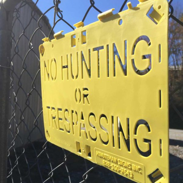 Molded For-ever Sign Yellow No Hunting or Trespassing installed on fence