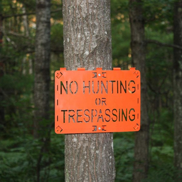 Molded Forever Sign Orange No Hunting or Trespassing installed on a tree