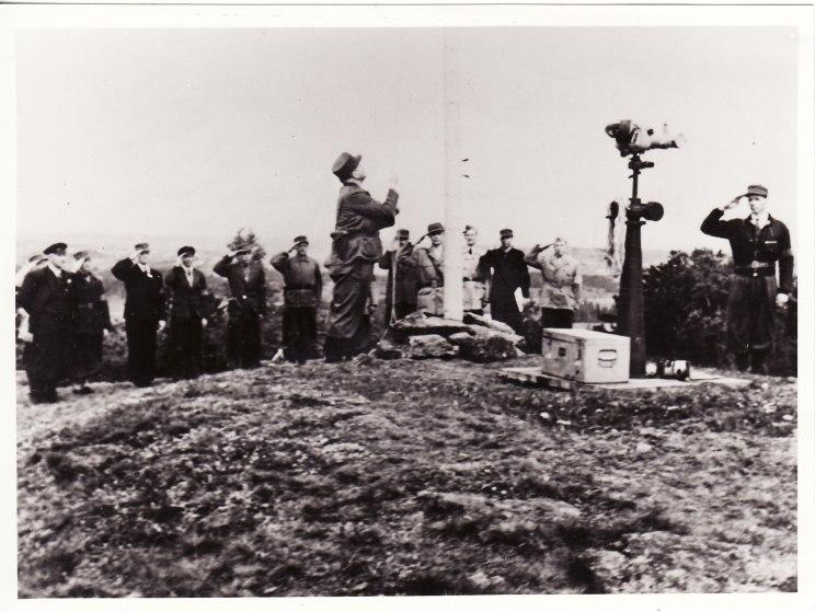 Flaggheising på Tinghaug 9. mai 1945 — nr. 2 fra venstre lærer A.M. Helle, nr. 7 nesttroppsjef Olav Bøe, flaggheiser kompanisjef Hans Lund Vinghøg, nr. 10 fra venstre områdesjef Ove Tollefsen, nr. 12 troppssjef Anker Marthinsen og lengst til høyre troppssjef Georg Flaaten.