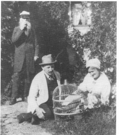 Olaf (t.v.) og Ragnvald Knudsen sammen med husholdersken Inger Andrea Nirisen i hagen på Svendsrød. Pappegøyen Polly i buret. Foto fra ca. 1920.